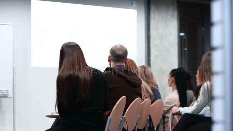 Audiencia en la sala de conferencias que mira una pantalla en blanco fotos de archivo