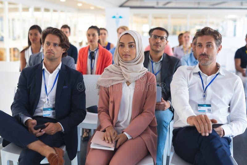 Audiencia que escucha el altavoz en un seminario del negocio fotografía de archivo
