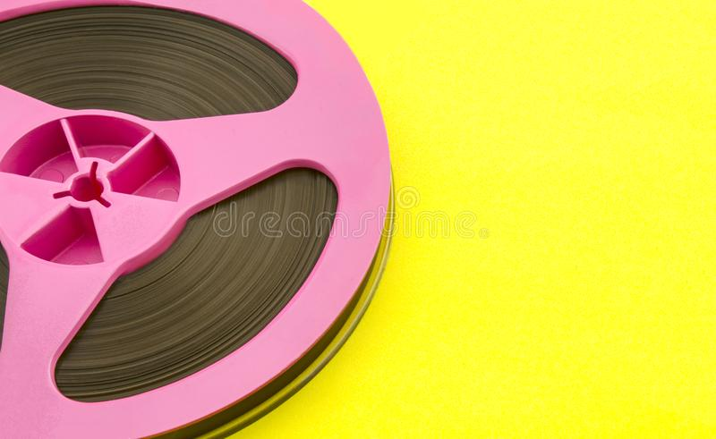 Audio bobina rosa d'annata con nastro adesivo di registrazione su fondo di carta giallo Stile d'avanguardia di Pop art immagini stock