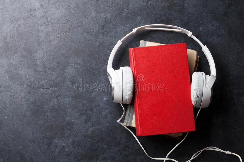 Audio book concept. Headphones and books over stone table. Top view with space for your text royalty free stock photography