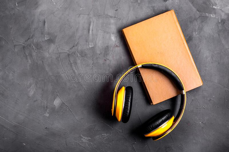 Audio book concept with headphones on grey table from above copy space royalty free stock photo