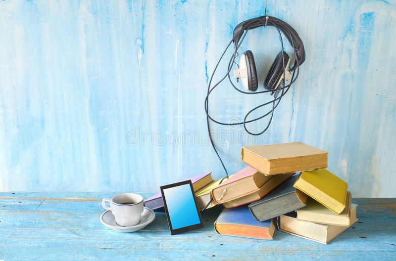 Audio book concept, with stack of books, headphones, smartphone and cup of coffee royalty free stock photo