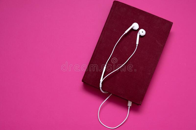 Audio book with headphones isolated on pink background stock images