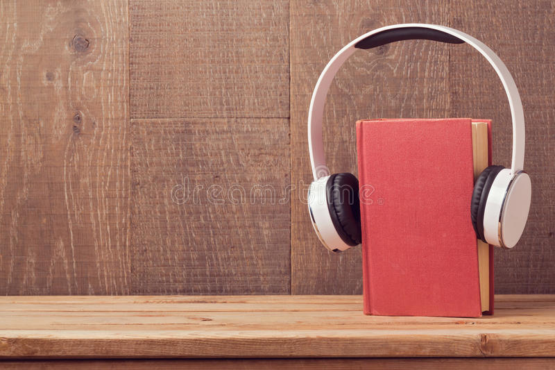 Audio books concept with old book and headphones royalty free stock photo