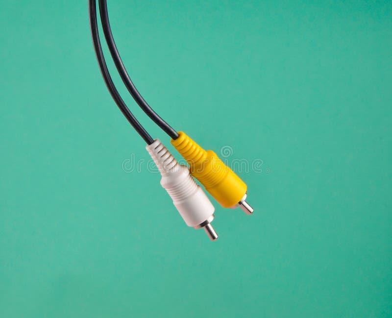 Audio/cable de vídeo blancos amarillos de RCA en fondo azul foto de archivo