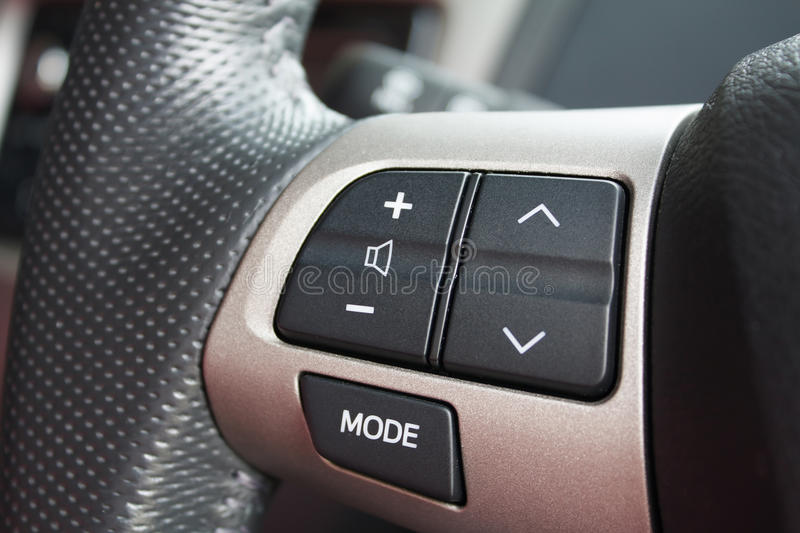 Audio control buttons on the steering wheel of modern car stock photography
