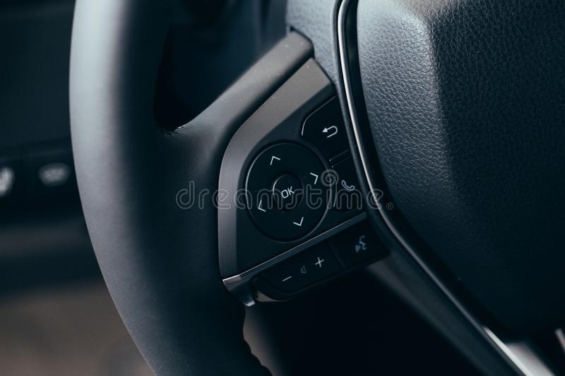 Audio control buttons on the steering wheel of a modern car stock photos