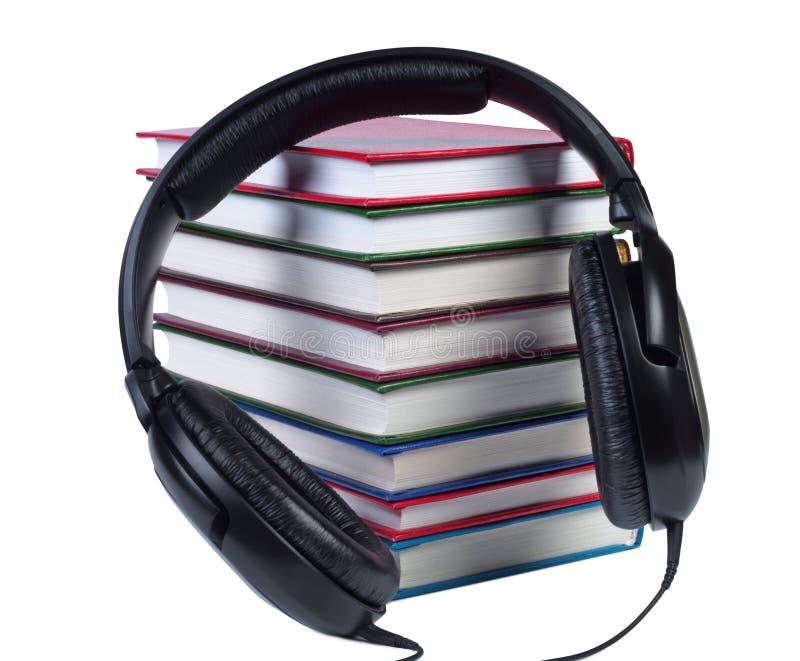 Audio cuffie su un mucchio dei libri con le coperture di colore. fotografie stock