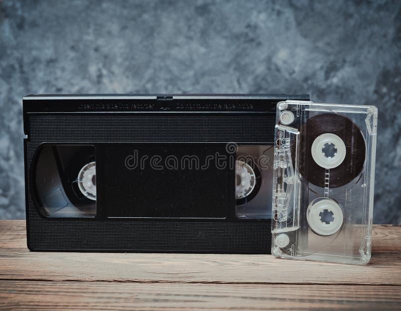 Audio en videocassetteclose-up op een houten plank tegen een grijze concrete muur Retro technologie voor het luisteren aan muziek royalty-vrije stock foto