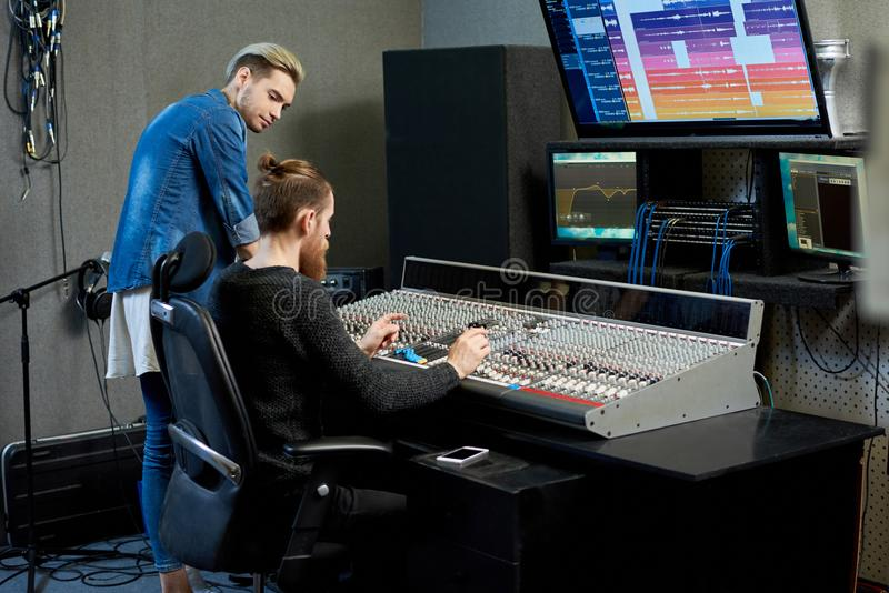 Audio engineer choosing sounds for track together with musician stock image