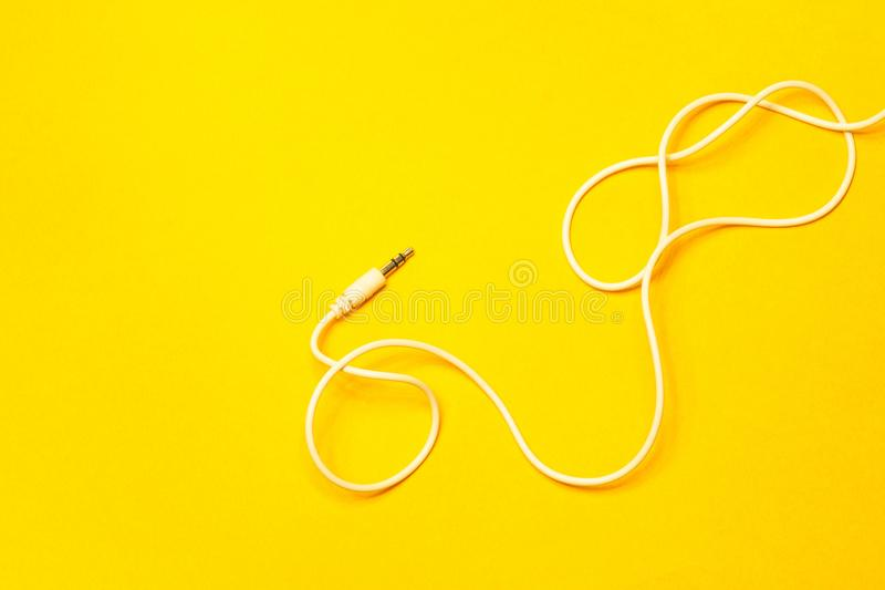Audio jack with white cable on yellow background stock photo