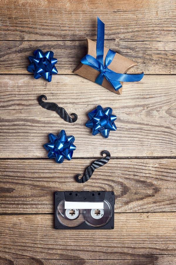 Audio kasety taśma z dekoracyjnym wąsy, łękami i prezentem na drewnianym tle, Ojca dnia poj?cie obraz royalty free