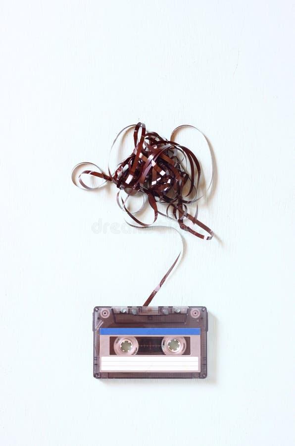 Audio kasety taśma z odejmuje out nagrywa nad błękitną textured drewno deską fotografia stock