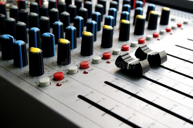 Audio mixer close-up with large black volume sliders stock image