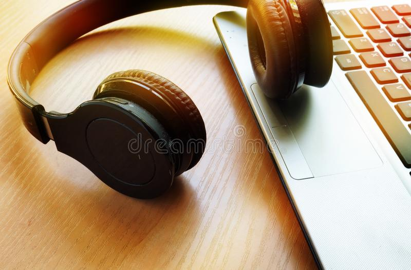 Audio podcast or music in internet concept. Headphones on a notebook stock photo