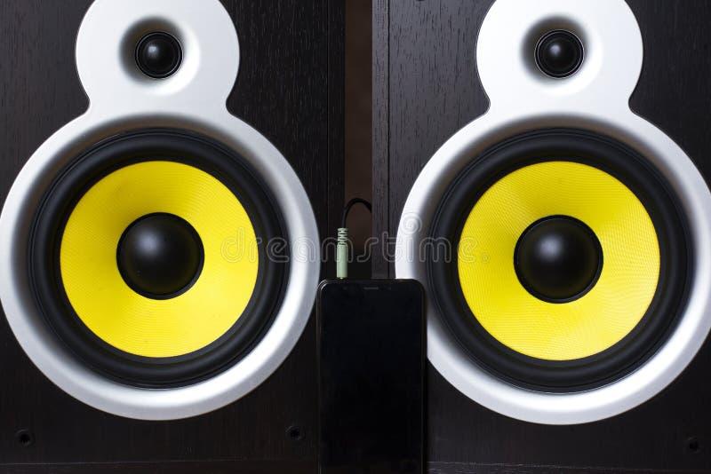 Audio sistema che gioca via gli altoparlanti gialli mobili e grandi collegati al telefono fotografia stock