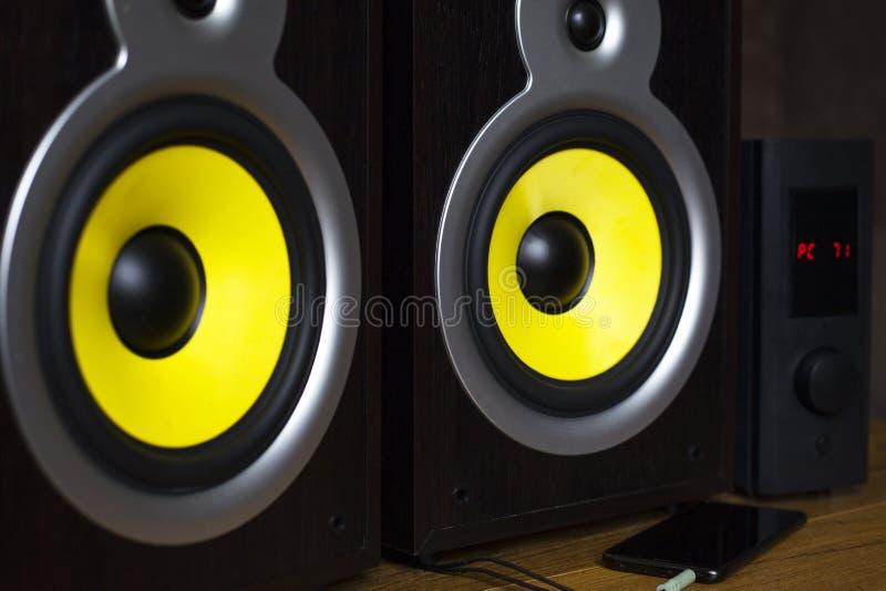 Audio sistema che gioca via gli altoparlanti gialli mobili e grandi collegati al telefono immagine stock libera da diritti