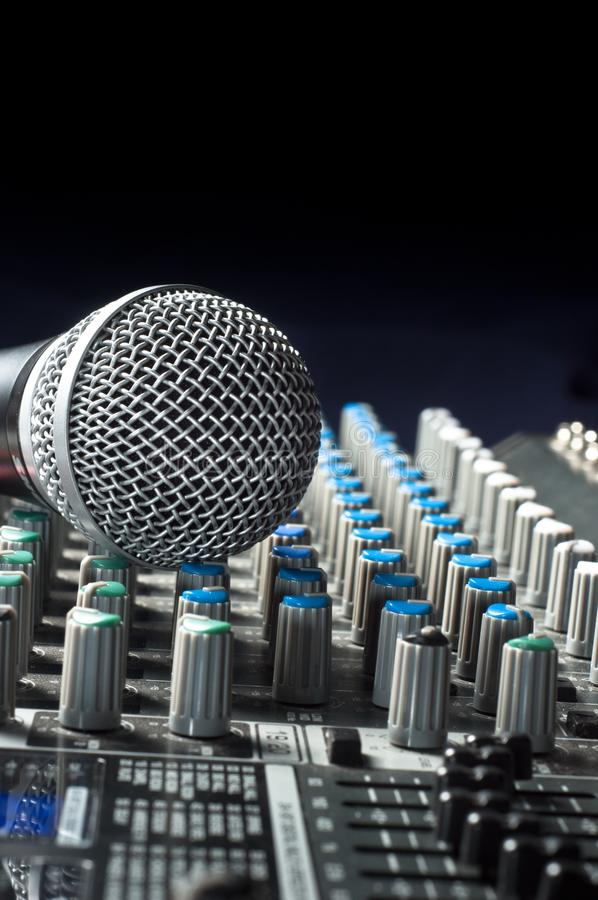 Audio sound mixer. Part of an audio sound mixer with a microphone stock photo