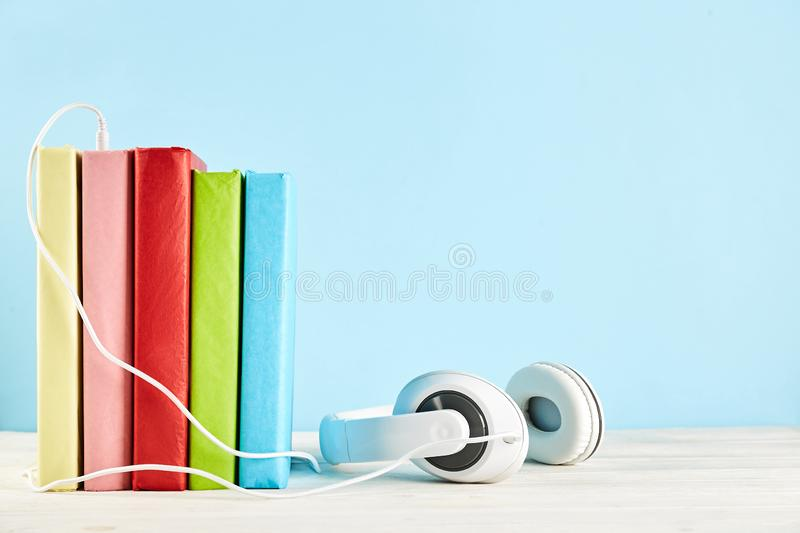 Audio vs. paper book concept. Reading versus listening. Books and headphones on table. Electronic audiobook vs regular paper book concept. Stack of different stock photo
