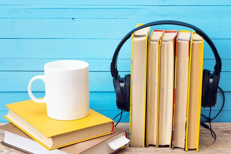 Audioboekconcept, boek en hoofdtelefoons en koffiemok over hout stock foto's