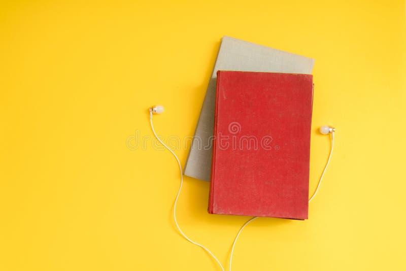 Audioboekconcept Hoofdtelefoons en boek over gele lijst backgr stock foto's