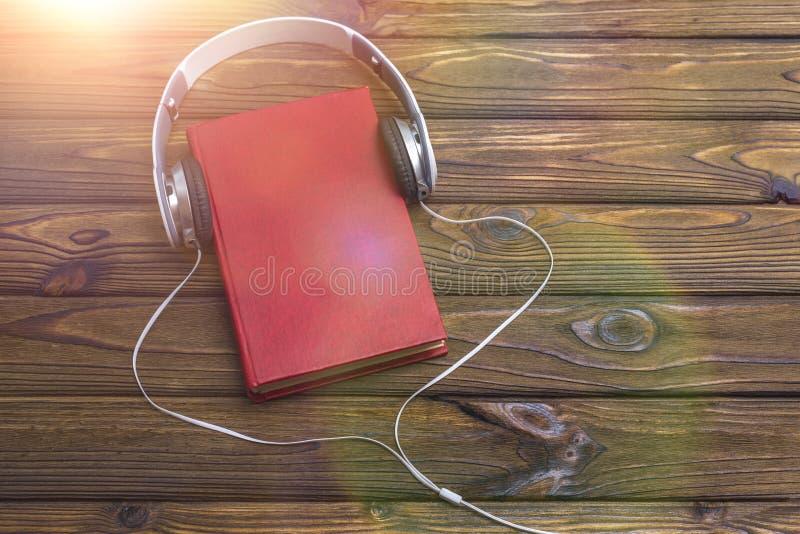 Audioboekconcept Hoofdtelefoons en oud boek over houten lijst royalty-vrije stock afbeelding