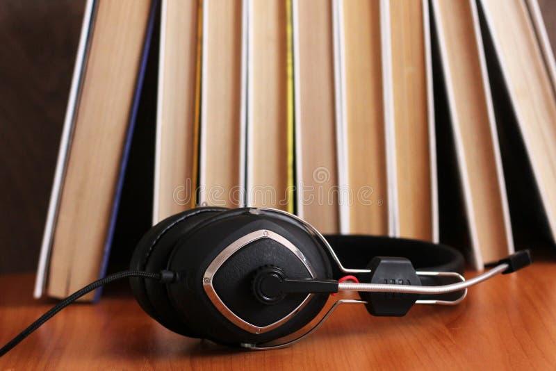 Audioboekconcept Hoofdtelefoons en oud boek over houten lijst royalty-vrije stock foto