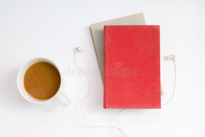 Audioboekconcept Hoofdtelefoons, koffie en hard dekkingsboek over stock foto