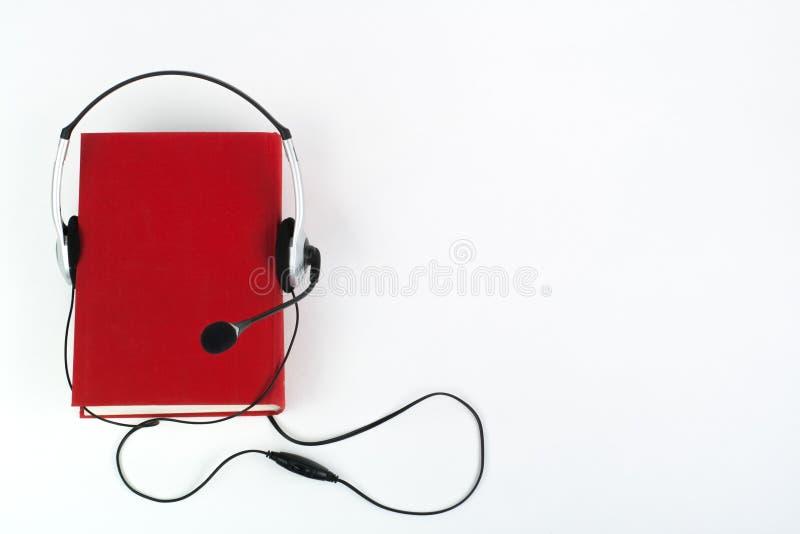 Audiobook στο άσπρο υπόβαθρο Τα ακουστικά βάζουν πέρα από το κόκκινο βιβλίο βιβλίων με σκληρό εξώφυλλο, κενή κάλυψη, διάστημα αντ στοκ φωτογραφίες