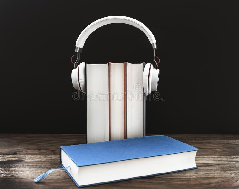 Audiobook concept with headphones on hardcover books against dark background stock photography