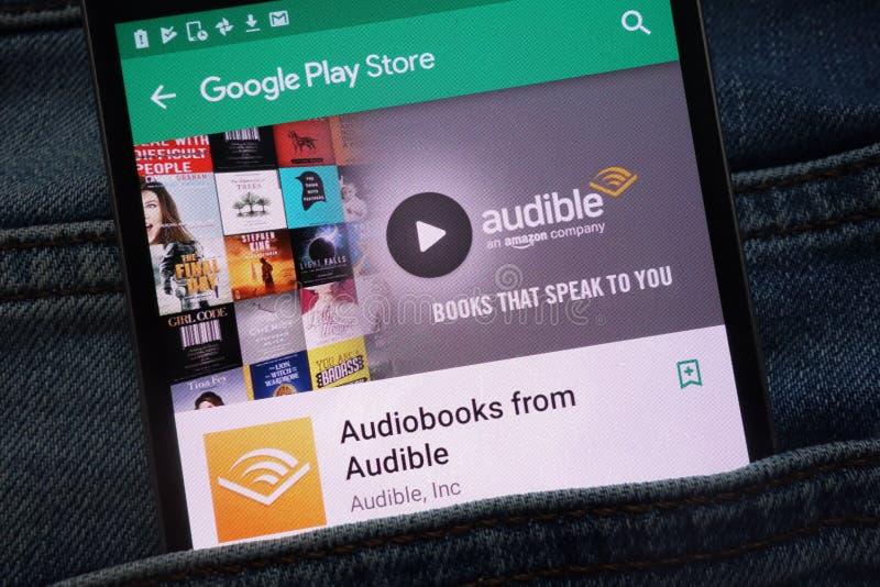 Audiobooks do app audível no Web site do Google Play Store indicado no smartphone escondido no bolso das calças de brim fotografia de stock royalty free