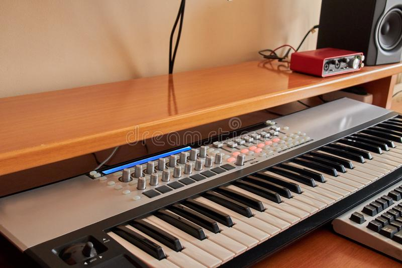 Audiohauptstudio ausgerüstet mit Midi-Tastatur, -monitoren und -Soundkarte stockbilder