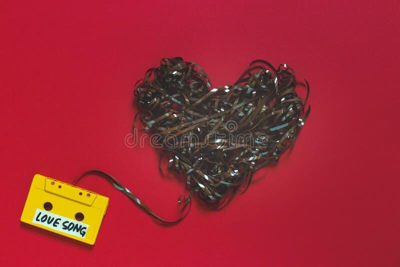 Audiokassette mit dem Aufschrift-Liebeslied auf einem roten Hintergrund Retro- Technologie-Romance Konzept lizenzfreie stockfotos