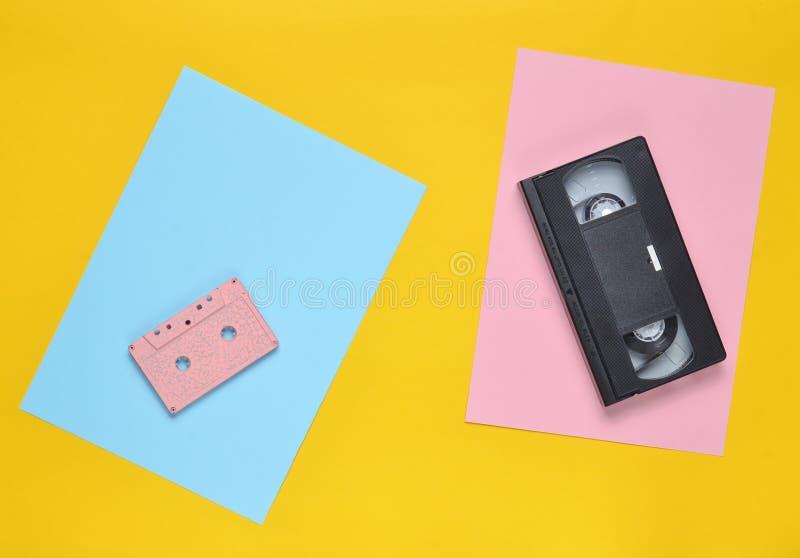 Audiokassetten- und Videokassette auf einem farbigen Papierhintergrund Retro- Unterhaltungstechnologie von den achtziger Jahren B stockbilder