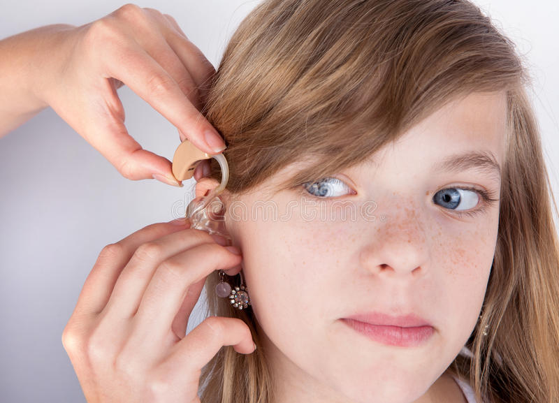Audiologist fitting a hearing aid to an adorable young girl patient stock photos