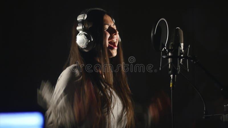 Audioopnamestudio Vrouw met hoofdtelefoons en studiomicrofoon het zingen stock afbeelding