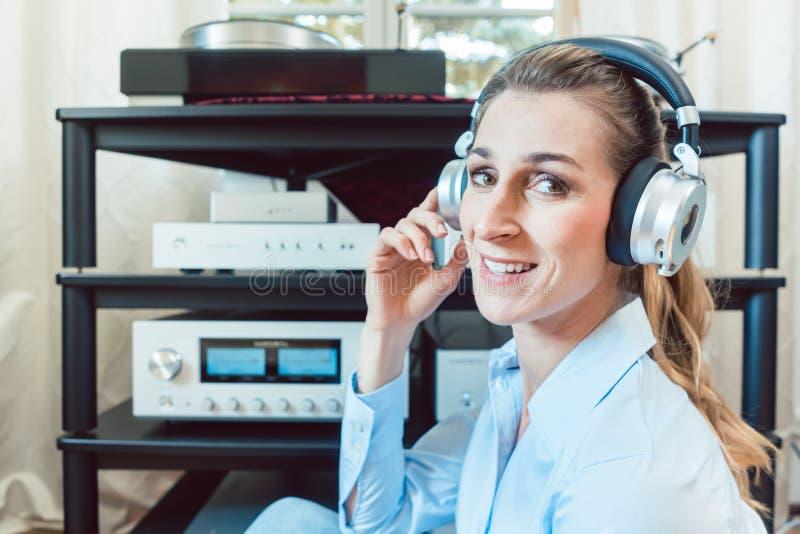 Audiophile kvinna som tycker om musik i hennes hem arkivfoton