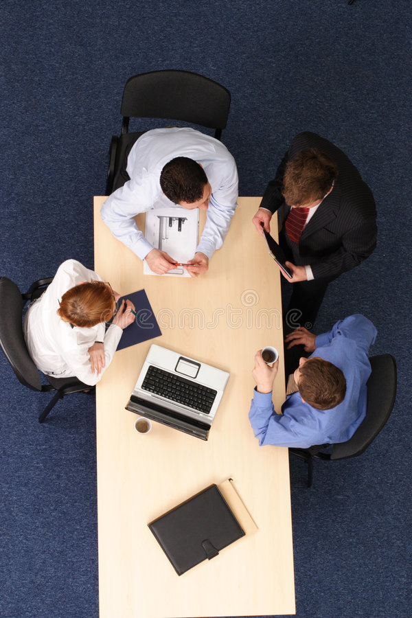Audit. Businesspeople gathered around a table for a meeting, brainstorming. Aerial shot taken from directly above the table stock photography