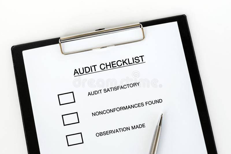 Audit Checklist. On attached on Clip board and pen on white background stock photo