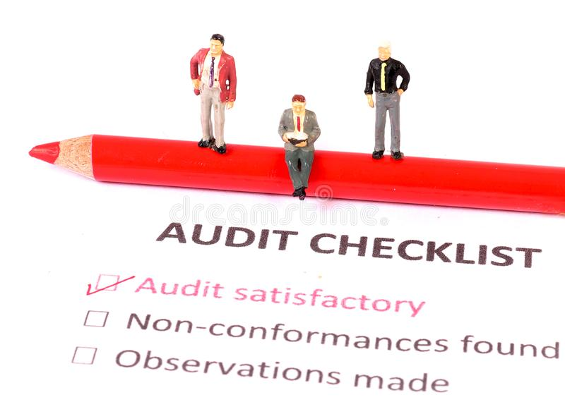 Audit checklist. Beautiful shot of figurines standing on audit checklist royalty free stock images