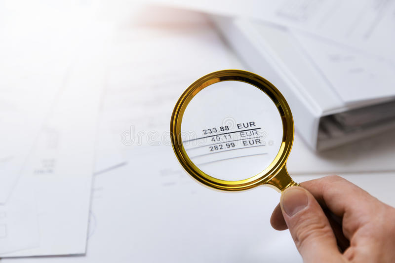 Audit concept - auditor checking bills with magnifying glass. In a hand royalty free stock photo