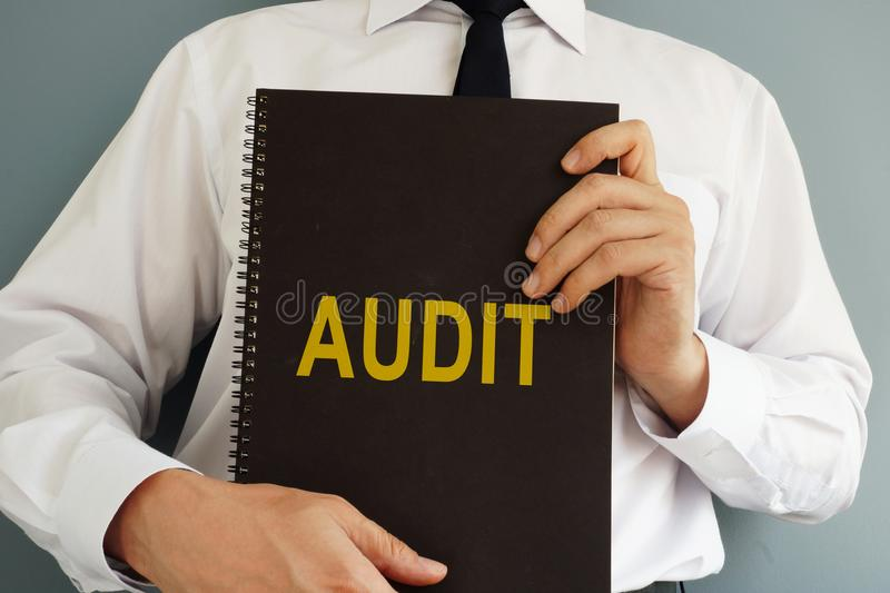 Audit concept. Auditor holding book. royalty free stock image