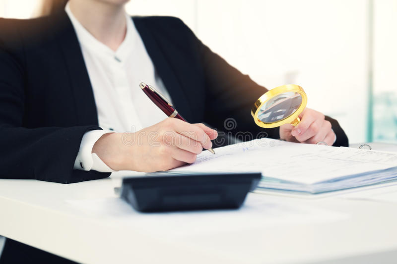 Audit concept - auditor with magnifying glass inspecting. Documents in office stock photos