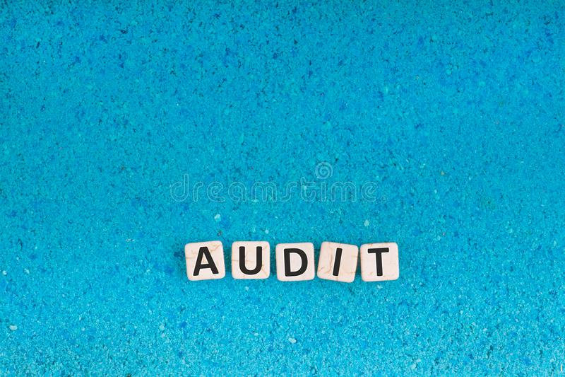 Audit word on stone. Audit word write in square white stone on blue sand, free space for your text royalty free stock image