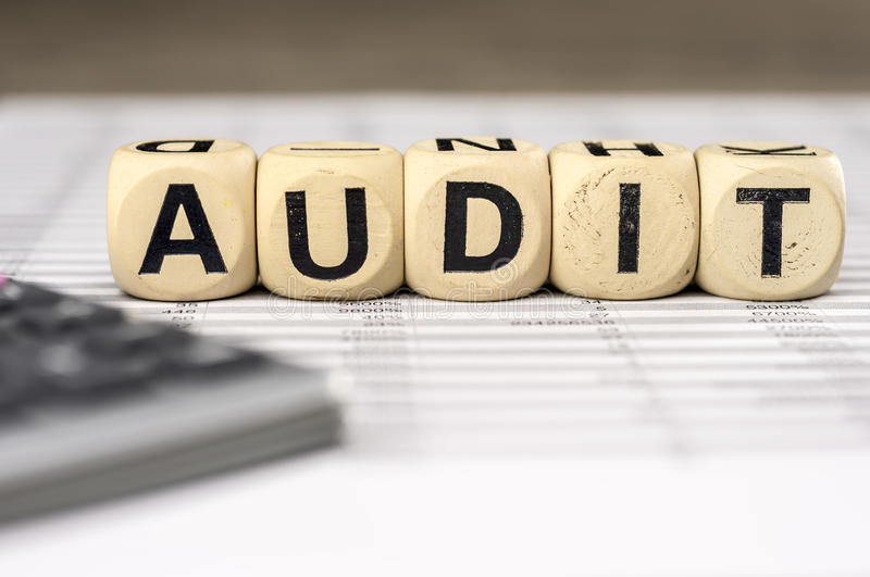 Audit word whith calculator and balance sheet. Calculator and balance sheet pages. The word audit assembled with wooden letter blocks stock photography
