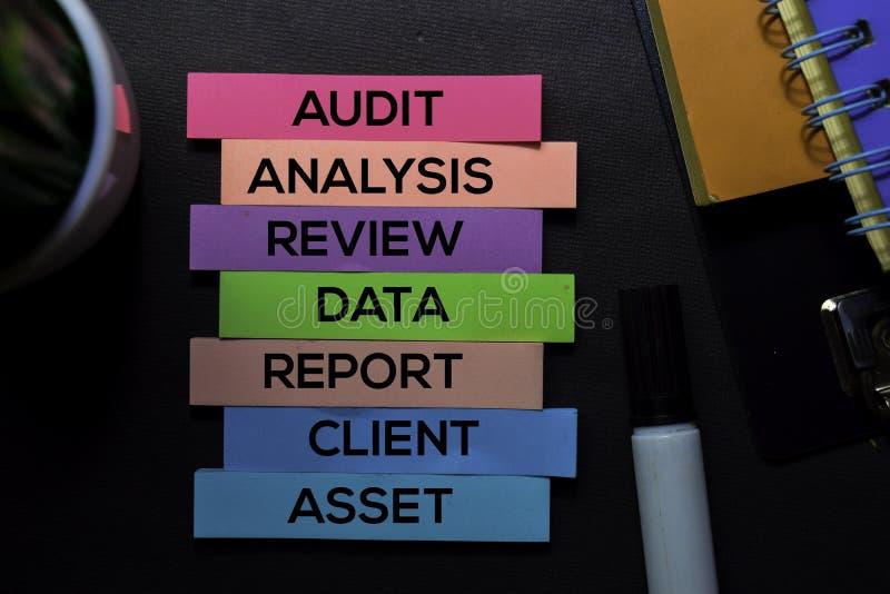 Auditoría, análisis, estudio, datos, informe, cliente, texto del activo en las notas pegajosas aisladas en el escritorio negro Co fotografía de archivo