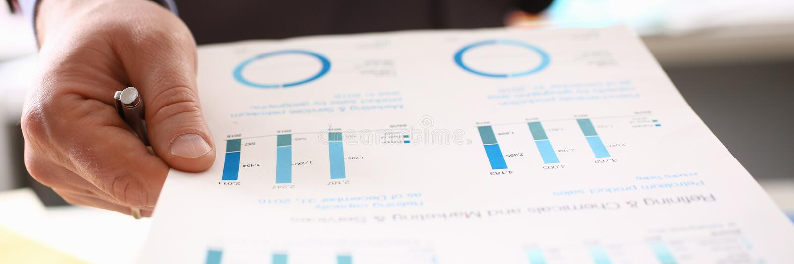 Auditor Calculating Tax Income Using Business Data. Caucasian Man Checking Documents at Workspace. Salary Accounting with Colorful Graph. Audit Group Company royalty free stock photography