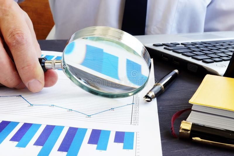 Auditor with magnifying glass checking financial report. stock images