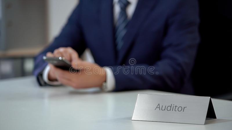 Auditor working on smart phone, proposing services online, chatting with client. Stock photo stock photography