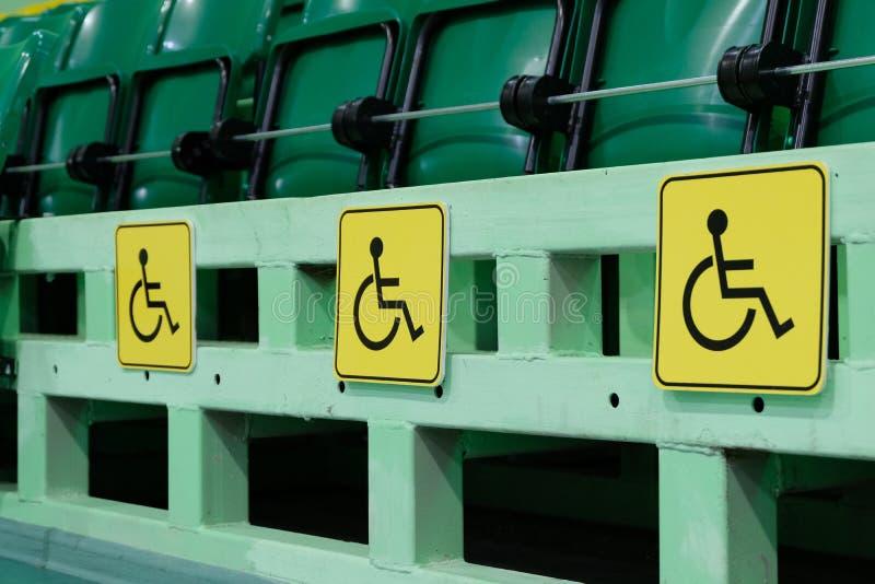 Auditorio con filas de sillas verdes Tres muestras amarillas que denotan los lugares para el discapacitado en el complejo de los  fotos de archivo libres de regalías